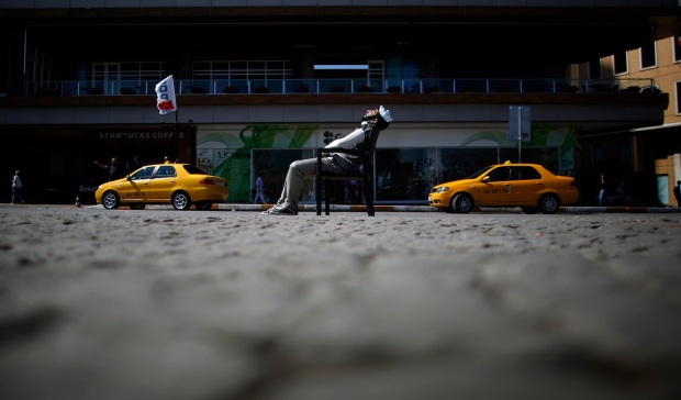 Protester wearing a Guy Fawkes mask sleeps on a chair at Taksim Square in central Istanbul