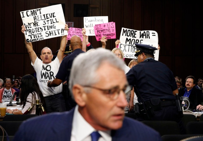 Anti-war protesters hold up signs as U.S. Secretary of Defense Chuck Hagel takes his seat to testify at the Senate Armed Services Committee hearing on the U.S. policy toward Iraq and Syria and the threat posed by the ISIL on Capitol Hill in Washington